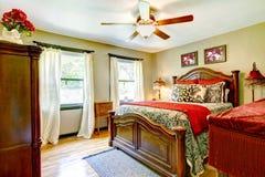 有红色和金内部的典雅的卧室。 免版税图库摄影
