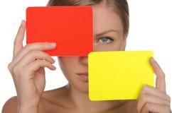 有红色和黄牌的年轻美丽的妇女 免版税库存照片