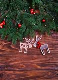 有红色响铃的圣诞节诗歌选和在木背景的两头鹿 平的位置,顶视图 免版税图库摄影