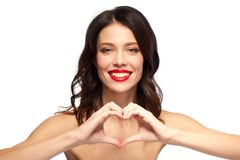 有红色唇膏和手心脏的美丽的妇女 库存照片