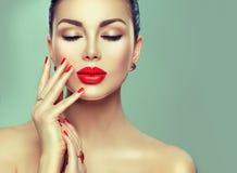有红色唇膏和红色钉子的秀丽时尚性感的妇女 免版税库存图片
