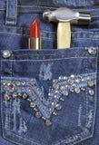 有红色唇膏和锤子接近的女工蓝色牛仔裤 免版税库存图片