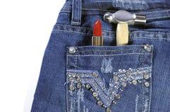 有红色唇膏和锤子的女工蓝色牛仔裤 免版税库存照片