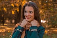 有红色唇膏的微笑的美丽的女孩看起来去并且保留手围巾 免版税库存图片
