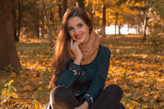 有红色唇膏的美丽的女孩在您的嘴唇和坐在秋天的温暖的围巾停放草坪微笑 免版税库存图片
