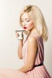 有红色唇膏的美丽的微笑的愉快的性感的典雅的女孩在减速火箭的样式的一件桃红色礼服喝从的茶咖啡小杯子 免版税库存照片