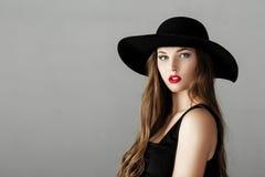 有红色唇膏的美丽的性感的妇女在黑帽会议 免版税库存图片