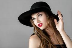 有红色唇膏的美丽的性感的妇女在黑帽会议 库存图片