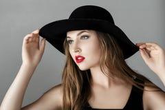 有红色唇膏的美丽的性感的妇女在黑帽会议 库存照片
