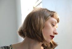 有红色唇膏的美丽,哀伤的妇女 免版税库存照片