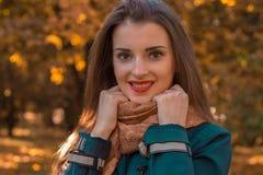 有红色唇膏的迷人的女孩在拿着手和微笑的围巾的嘴唇 免版税库存图片