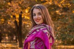 有红色唇膏的迷人的女孩在肩膀的公园围巾站立并且对krupnyy计划微笑 库存照片