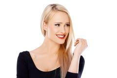 有红色唇膏的逗人喜爱的白肤金发的女孩在她的嘴唇 免版税库存照片