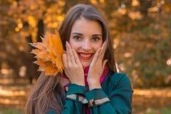 有红色唇膏的年轻可爱的女孩在面孔特写镜头附近微笑并且拿着您的手棕榈  库存图片
