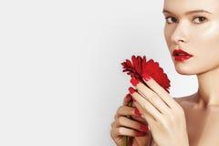 有红色嘴唇、唇膏和美丽的红色花的特写镜头秀丽画象性感的妇女 温泉干净的皮肤 沙龙构成 库存照片