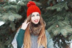 有红色嘴唇和一个被编织的帽子的年轻美丽的女孩在冬天c 图库摄影