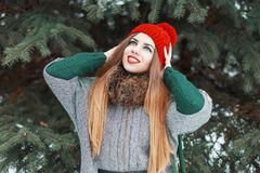 有红色嘴唇和一个被编织的帽子的年轻美丽的女孩在Th走 库存照片