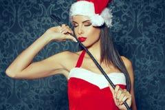 有红色嘴唇摆在的性感的圣诞老人妇女室内与鞭子在基督 库存图片