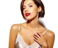 有红色嘴唇的美丽的愉快的逗人喜爱的性感的深色的妇女在白色背景的睡衣女用贴身内衣裤 库存照片