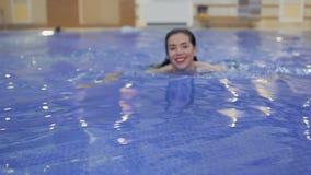 有红色嘴唇的迷人的夫人在水池游泳 影视素材