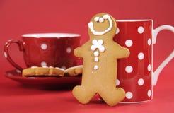 有红色圆点咖啡杯和茶杯的姜饼人 免版税库存图片