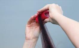 有红色圆环和红色卷发的人的Woman's手 免版税库存照片