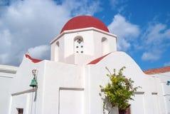 有红色圆顶的教会在米科诺斯岛,希腊 教堂在晴朗室外的大厦建筑学 多云蓝天的白色教会 库存照片