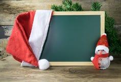 有红色圣诞老人帽子和圣诞节雪人的黑板在老w戏弄 库存照片