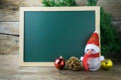 有红色圣诞老人帽子和圣诞节雪人的黑板在老w戏弄 免版税库存照片