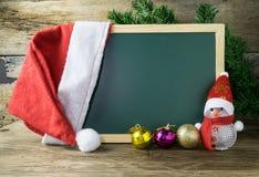 有红色圣诞老人帽子和圣诞节雪人的黑板在老w戏弄 图库摄影