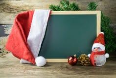 有红色圣诞老人帽子和圣诞节雪人的黑板戏弄 库存照片