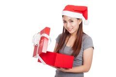 有红色圣诞老人帽子的亚裔女孩打开礼物盒和微笑 免版税库存图片