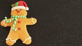 有红色圣诞老人帽子绿色和白色围巾的姜饼人在与写空间的黑背景 图库摄影