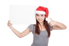 有红色圣诞老人帽子赞许的亚裔女孩与一个空白的标志 库存照片