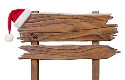 有红色圣诞老人的帽子的木标志板材 免版税库存图片