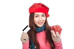 有红色圣诞节帽子、信用卡和礼物盒的亚裔女孩 免版税库存图片