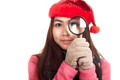 有红色圣诞节帽子和放大镜的亚裔女孩 免版税图库摄影