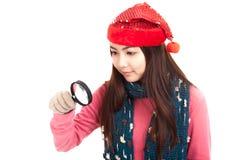 有红色圣诞节帽子和放大镜的亚裔女孩 库存照片
