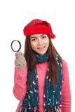有红色圣诞节帽子和放大镜的亚裔女孩 库存图片
