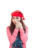 有红色圣诞节帽子和放大镜的亚裔女孩 免版税库存照片