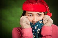 有红色圣诞节帽子感受寒冷的亚裔女孩 免版税库存图片