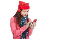 有红色圣诞节帽子接触巧妙的电话的亚裔女孩 图库摄影