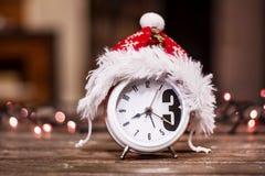 有红色圣诞节帽子的减速火箭的闹钟 免版税库存照片