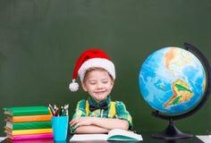 有红色圣诞节帽子的愉快的男孩在教室 免版税库存图片