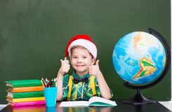 有红色圣诞节帽子的愉快的男孩在显示赞许的教室 图库摄影