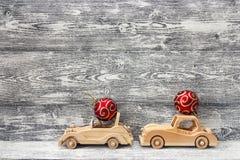 有红色圣诞节球的两辆木玩具汽车在屋顶 灰色w 免版税库存照片