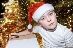 有红色圣诞节盖帽文字信件的六岁的逗人喜爱的小男孩给在户内圣诞树附近的圣诞老人 明亮的新年 图库摄影
