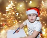 有红色圣诞节盖帽的六岁的逗人喜爱的小男孩写信的给圣诞老人在圣诞树附近户内 聪慧的新的Ye 免版税图库摄影
