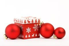 有红色圣诞节装饰的红色圣诞节礼物和在白色背景的三个红色暗淡圣诞节球 有christm的圣诞节礼物 免版税库存图片