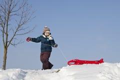 有红色塑料爬犁的男孩在多雪的小山 免版税图库摄影
